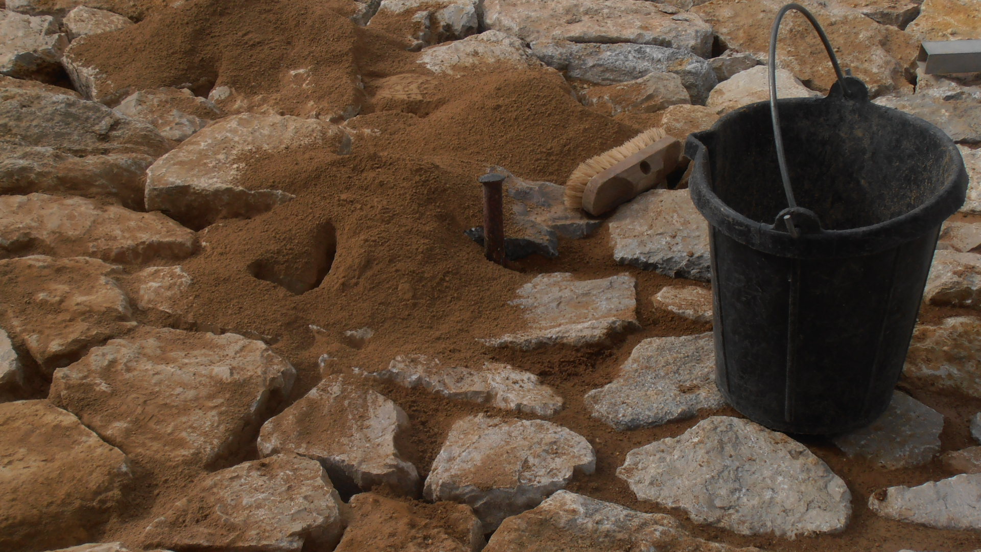 rejuntant amb argila i compactant amb tascó